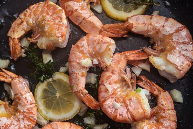 crevettes rôties à la crevette de tigre avec de l'ail, du citron et des herbes dans une poêle noire, fond de cuisson, vue en gr photo stock