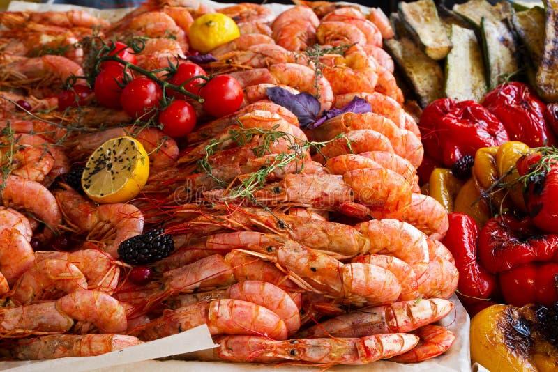 Crevettes roses, citron grillé et légumes étant servis sur la stalle de nourriture sur l'événement international de festival de n photo stock
