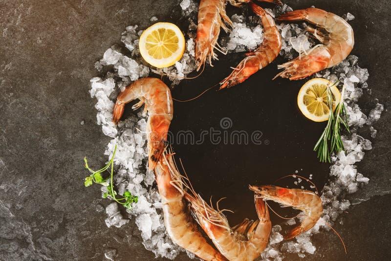 Crevettes roses crues fraîches ou grandes crevettes avec les épices et la glace sur la pierre d'ardoise sur le fond en pierre fon photo stock