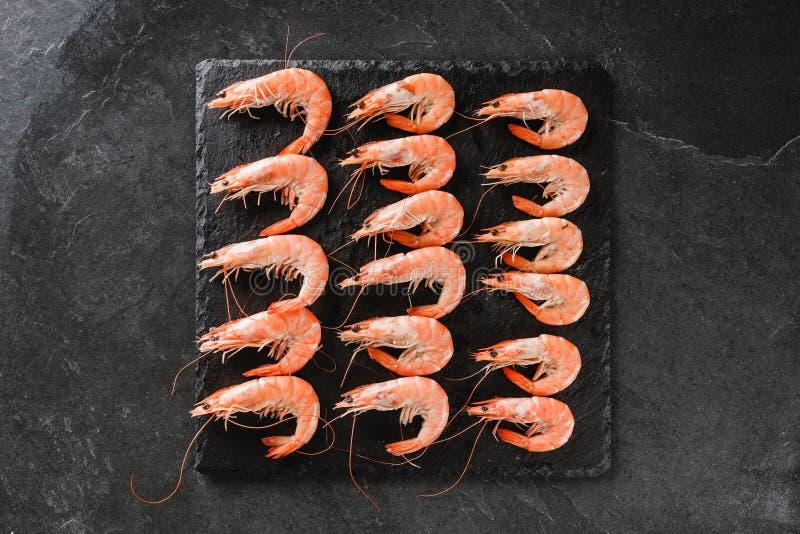 Crevettes roses crues fraîches ou crevettes rouges une autre taille sur la pierre d'ardoise au-dessus du fond en pierre foncé Fru photographie stock libre de droits