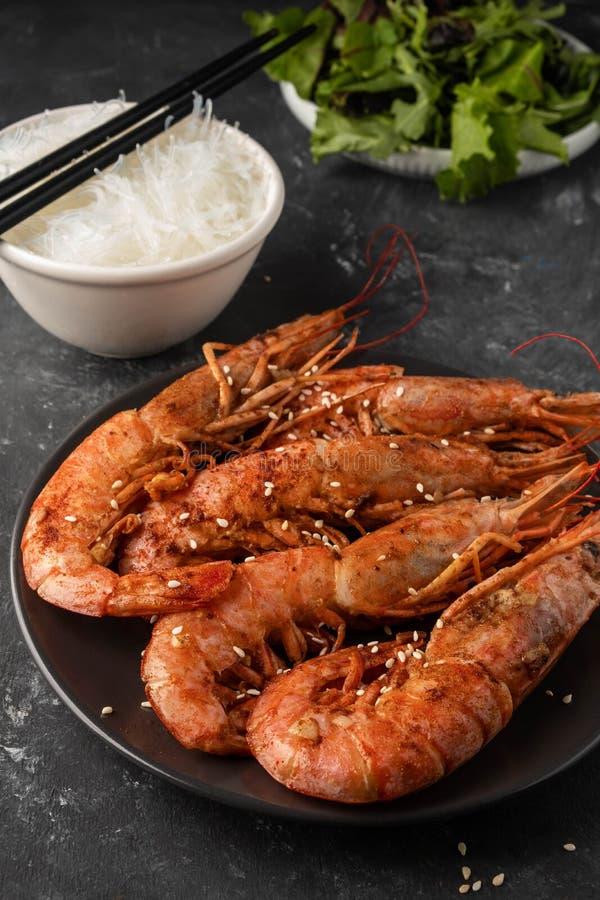 Crevettes roses grillées frites avec des feuilles de nouille et de laitue de riz, fond foncé photos libres de droits