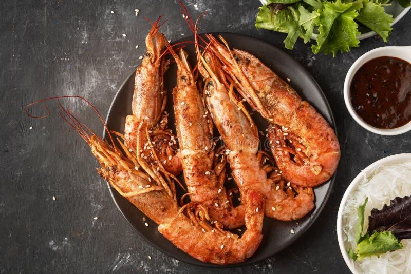 Crevettes roses grillées frites avec la nouille de riz, la sauce et la laitue, fond foncé image stock