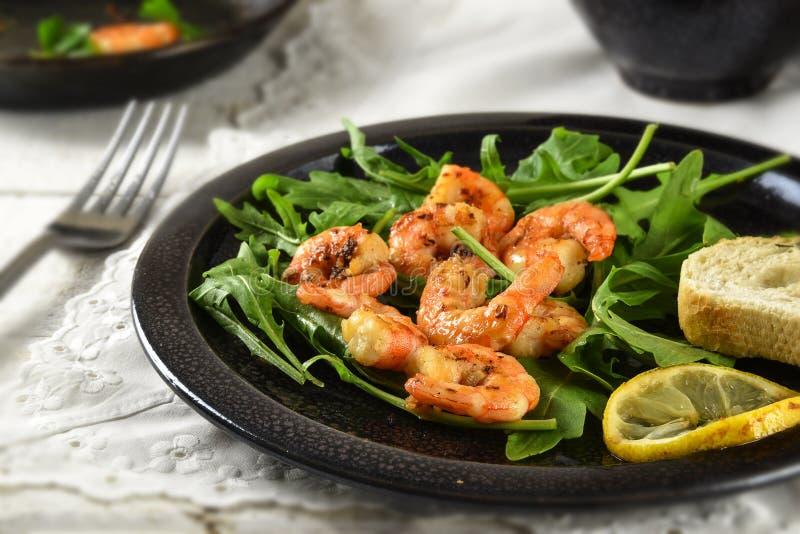 Crevettes roses ou crevettes rôties sur la salade de fusée de rucola avec le citron et photos stock