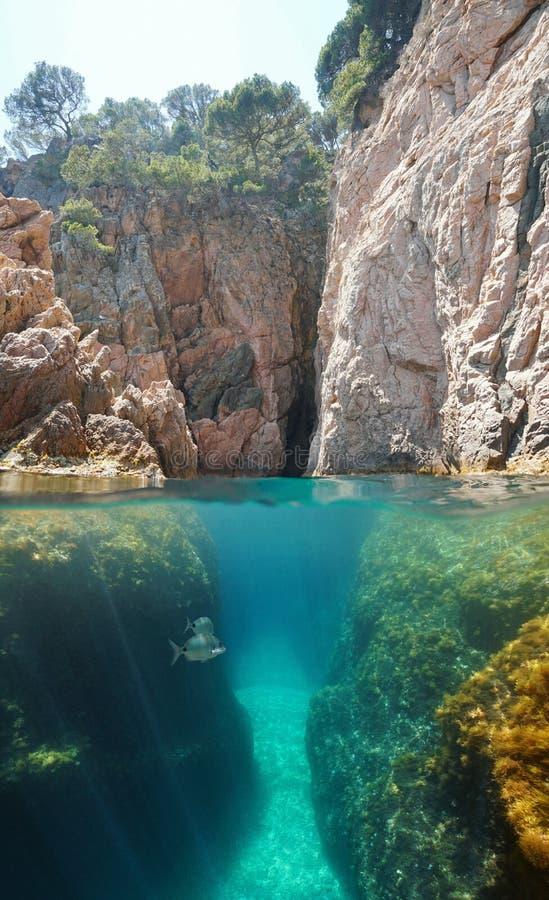 Crevice на скалистом побережье над и под водой стоковые изображения