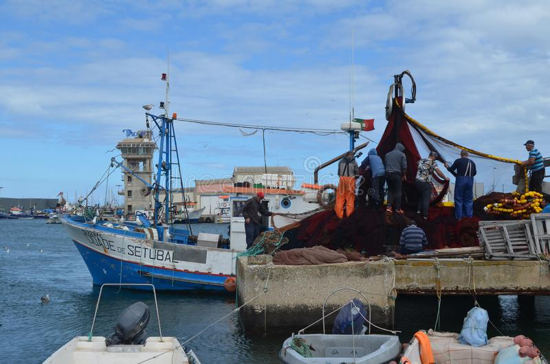 The crew of a purse seiner collects its nets in Olhao fishing harbour, Algarve, Southern Portugal. Olhão is a municipality and urban community in the stock image