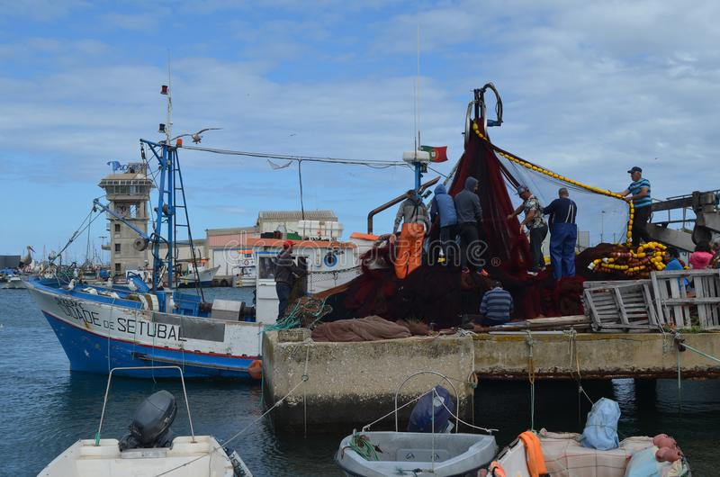 The crew of a purse seiner collects its nets in Olhao fishing harbour, Algarve, Southern Portugal. Olhão is a municipality and urban community in the Algarve stock photo