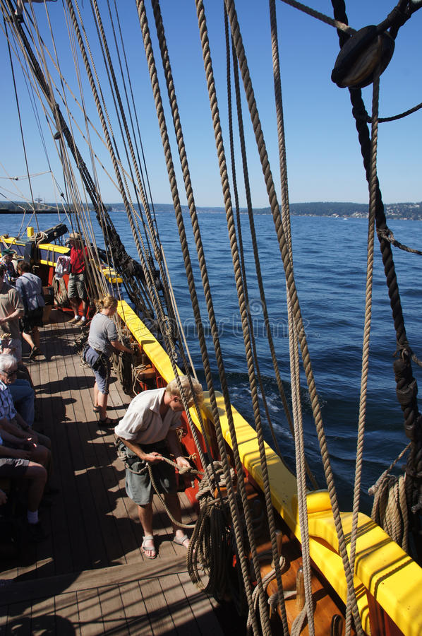The crew sets the sails of the Lady Washington royalty free stock photography