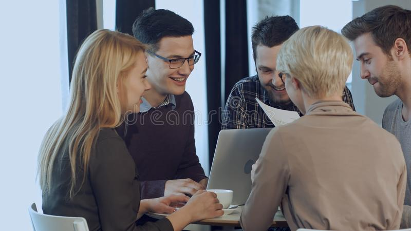 Crew of talented male and female business team resting having fun and joking during work break stock photography