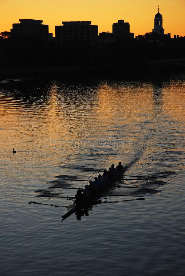 Crew Team on the Charles. A crew team of women rowers ply the waters of the Charles river at sunrise near Cambridge, Massachusetts royalty free stock photography