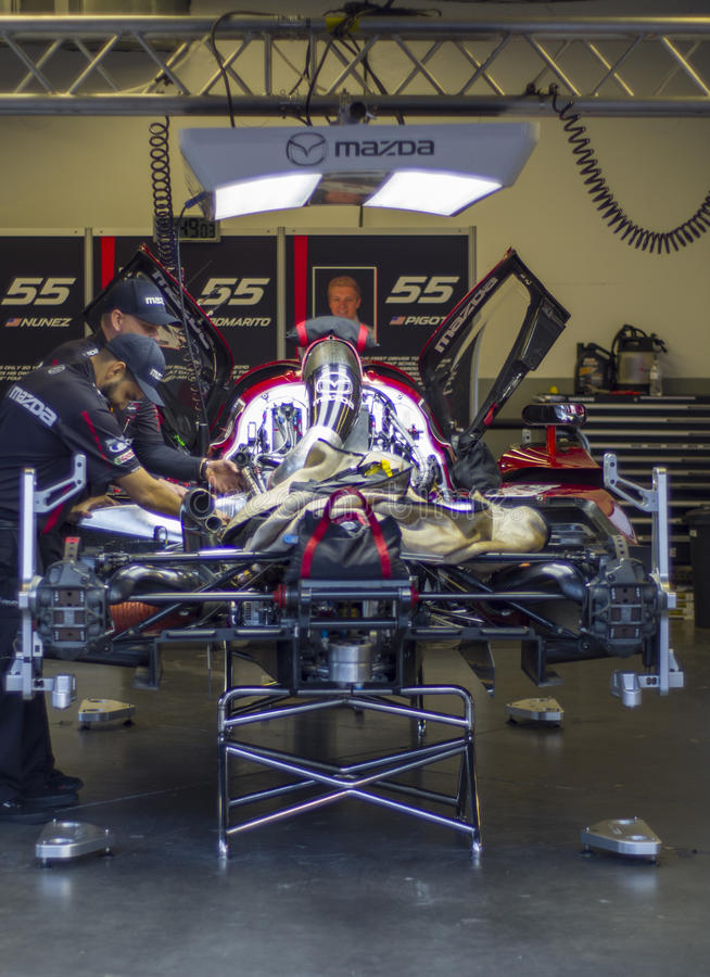 Crew works Mazda DP race car at Daytona Speedway Florida. Crew checks their Mazda DP prototype race car for the 2016 24 Hours of Daytona sports car race in royalty free stock photos