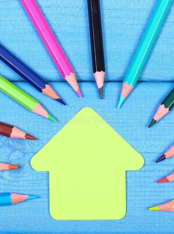 Creyones coloridos y forma de la construcción de escuelas en los tableros azules, accesorios de la escuela imagen de archivo libre de regalías