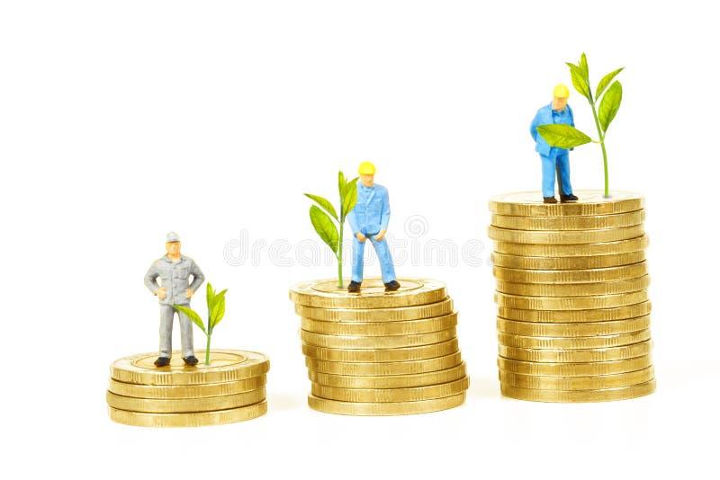Crezca las pequeñas plantas y al trabajador miniatura con la moneda de oro imagen de archivo