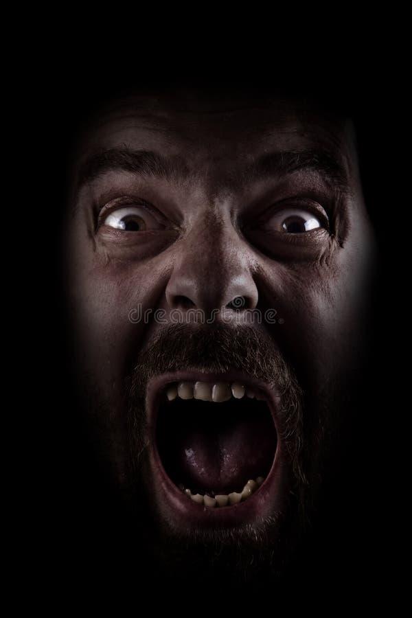 Cri perçant d'homme fantasmagorique effrayé dans l'obscurité images libres de droits