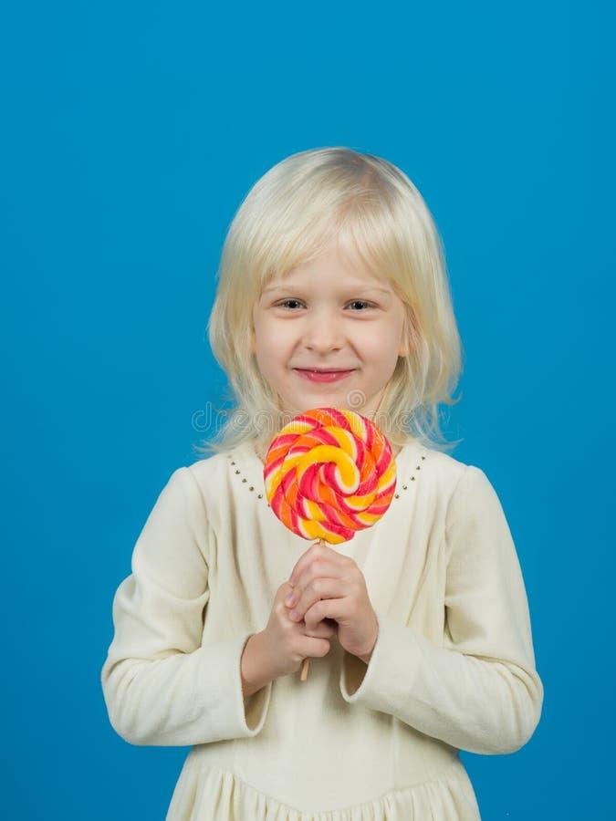 Criação corajosa dos doces duros Criança pequena com pirulito doce Pirulito pequeno da posse da menina na vara Menina feliz dos d imagens de stock royalty free