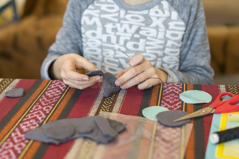 criação a menina costura o brinquedo feito do feltro A menina costura um rato cinzento A menina costura um brinquedo fotografia de stock