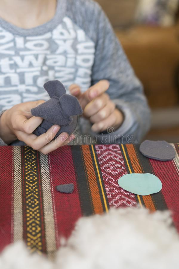 criação a menina costura o brinquedo feito do feltro A menina costura um rato cinzento A menina costura um brinquedo imagem de stock