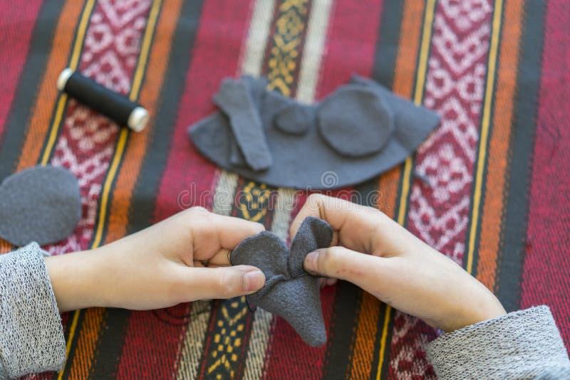criação a menina costura o brinquedo feito do feltro A menina costura um rato cinzento A menina costura um brinquedo fotos de stock