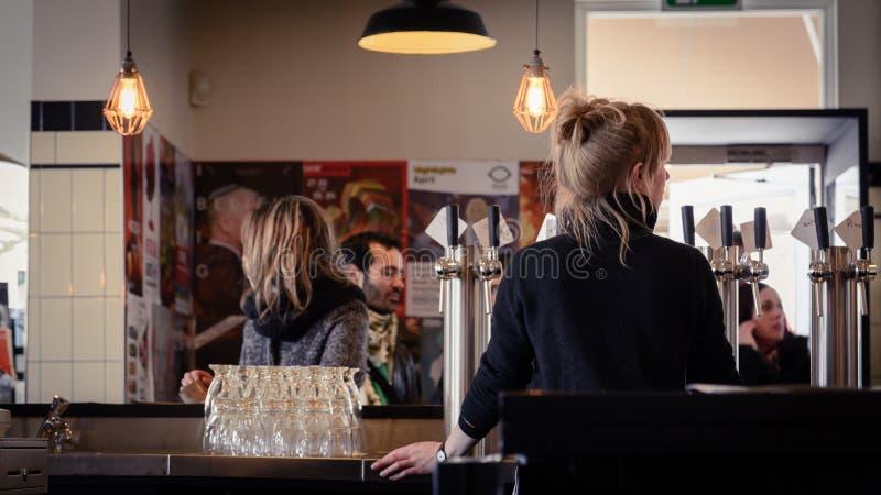 Criada de la barra en cervecería de t IJ de Brouwerij 'en Amsterdam Países Bajos En marzo de 2015 fotos de archivo