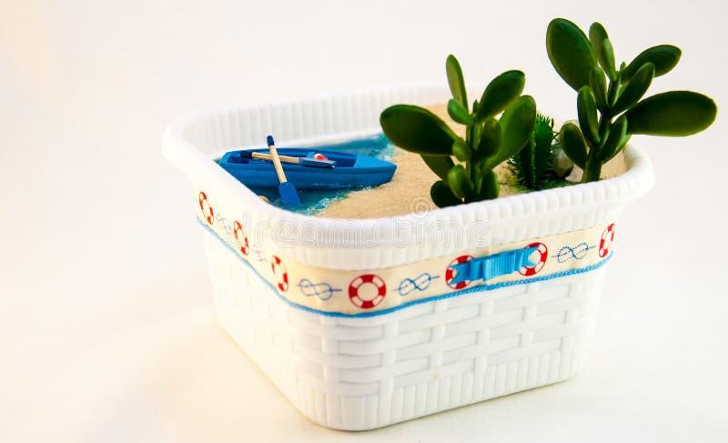 Criada de la mano, miniatura una playa con un barco en la orilla arenosa Agua azul con las cáscaras y las plantas imagen de archivo