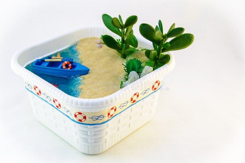 Criada de la mano, miniatura una playa con un barco en la orilla arenosa Agua azul con las cáscaras y las plantas fotografía de archivo libre de regalías