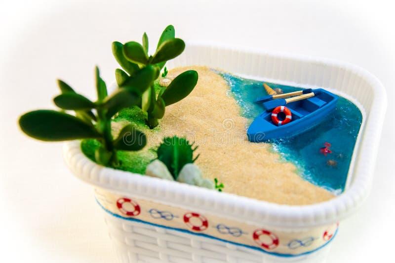 Criada de la mano, miniatura una playa con un barco en la orilla arenosa Agua azul con las cáscaras y las plantas foto de archivo libre de regalías