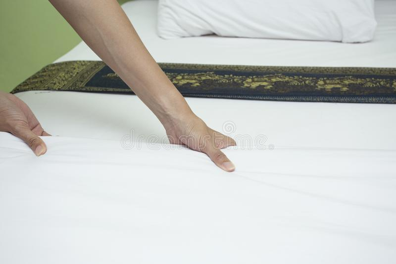 Criada que hace la cama en la habitación foto de archivo