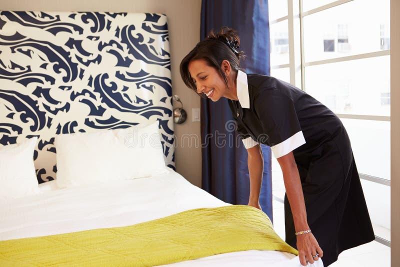 Criada Tidying Hotel Room y cama de la fabricación imágenes de archivo libres de regalías
