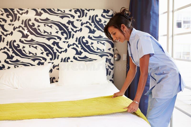 Criada Tidying Hotel Room y cama de la fabricación fotos de archivo