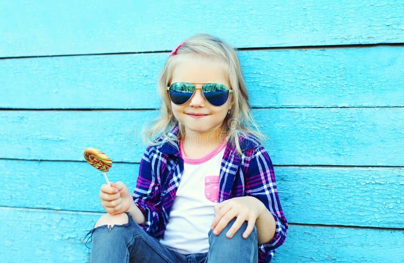 Download Criança à Moda Com O Pirulito Doce Do Caramelo Sobre O Azul Colorido Imagem de Stock - Imagem de feliz, cidade: 65576147