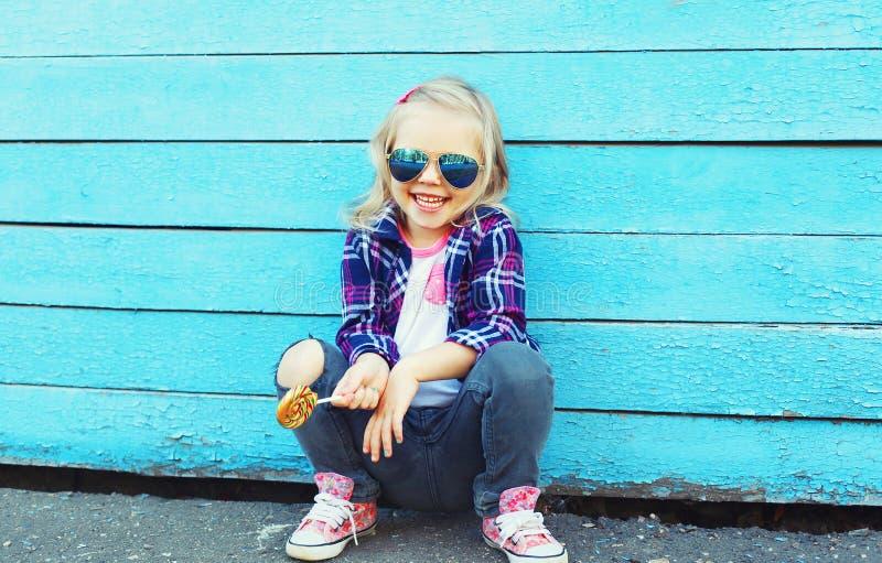 Download Criança à Moda Com O Pirulito Doce Na Cidade Sobre O Azul Colorido Foto de Stock - Imagem de vidros, pouco: 65576138
