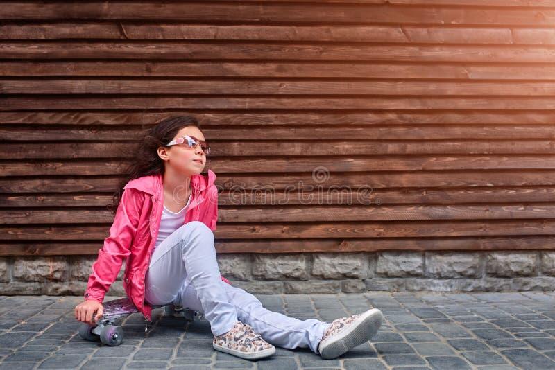 Criança à moda da menina que veste um revestimento cor-de-rosa do verão ou do outono, calças de brim brancas, óculos de sol fotografia de stock royalty free