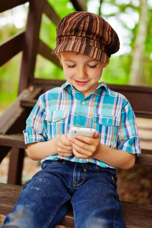 Criança à moda nova que joga jogos no telefone celular fotos de stock