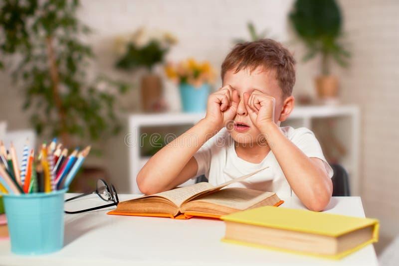 A criança é cansado da aprendizagem educação de casa, trabalhos de casa o menino fricciona seus olhos dos livros e dos livros de  fotografia de stock royalty free
