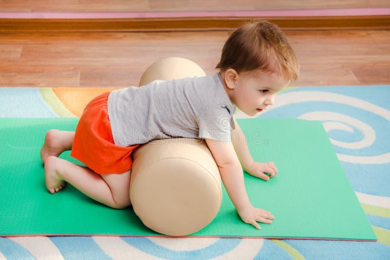 A criança é contratada nos esportes no gym fotos de stock
