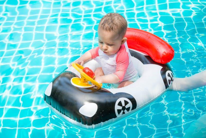 A criança é muito apaixonado sobre o processo Uma menina menos do que a criança de um ano está conduzindo um barco inflável na fo foto de stock