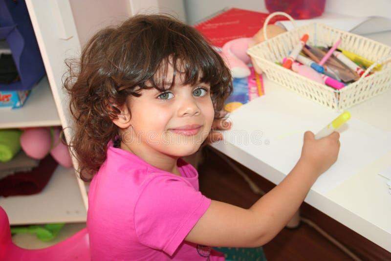 A criança é pintura no papel fotografia de stock