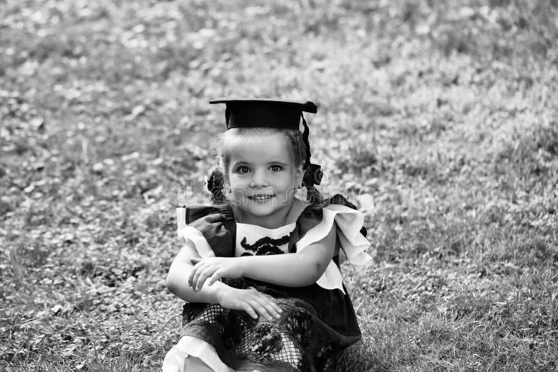 A criança é um gênio A criança é um prodígio de criança Menina bonito com cabelo longo no tampão preto da graduação fotos de stock