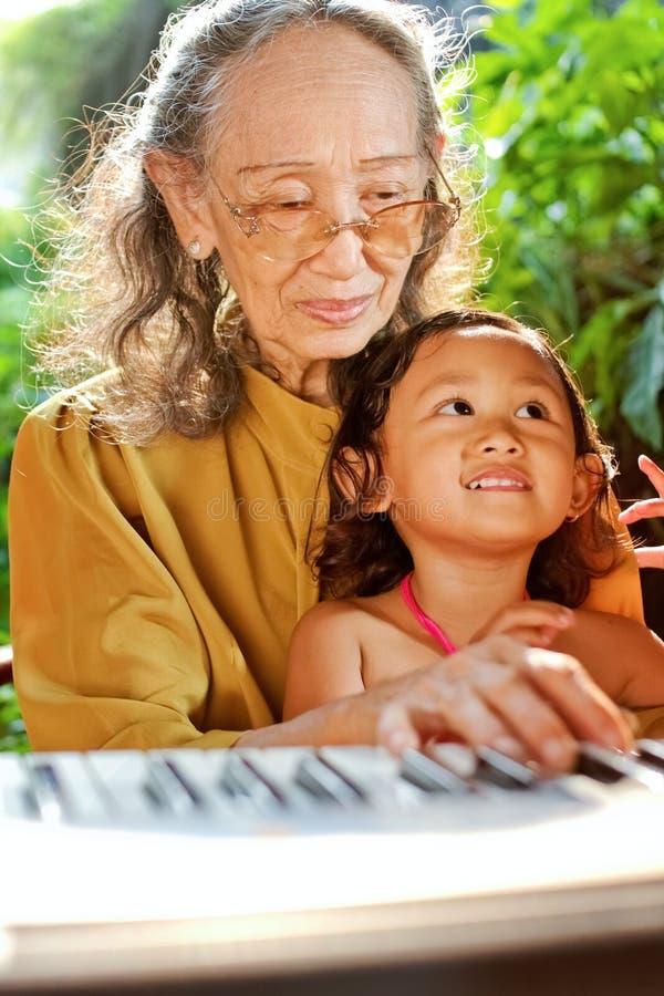 Criança étnica e avó que jogam o piano fotografia de stock