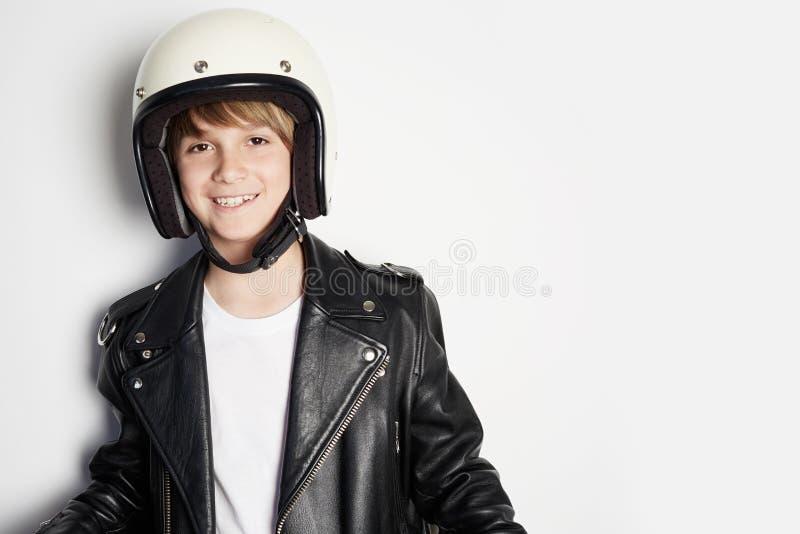 Criança adolescente alegre feliz nova no casaco de cabedal preto e no capacete branco do moto que sorri no fundo branco imagem de stock