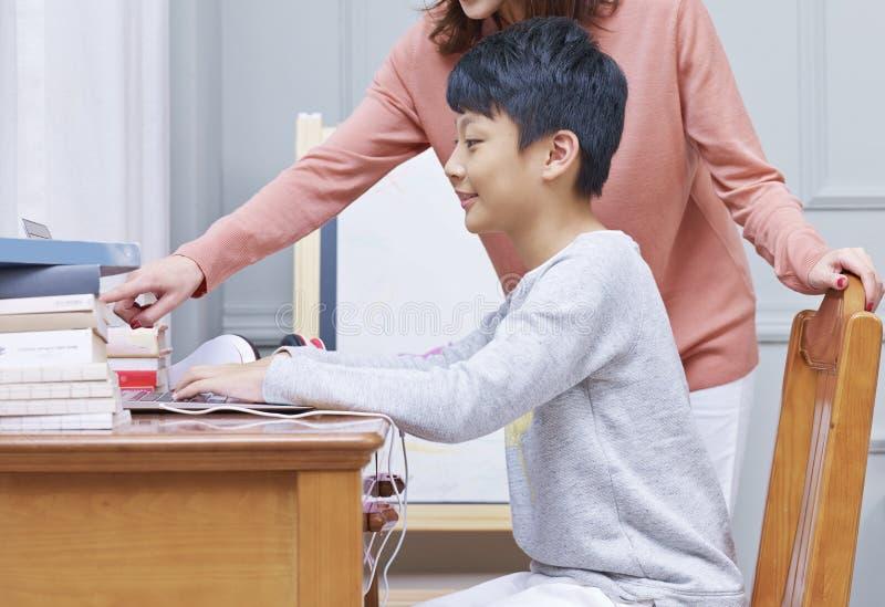 Criança adolescente da tutoria asiática da mãe, ensino eletrónico em casa imagens de stock royalty free