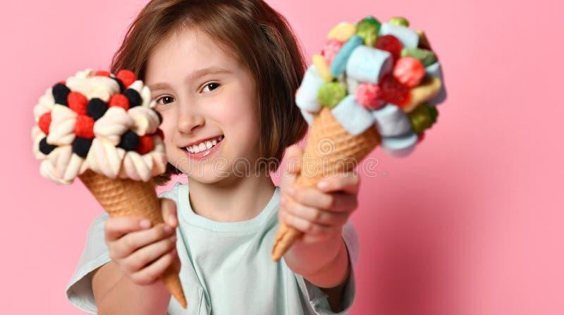 A criança adolescente de sorriso agradável da menina dá, oferece ou mostra-nos dois gelado grande no cone dos waffles com doce de fotos de stock
