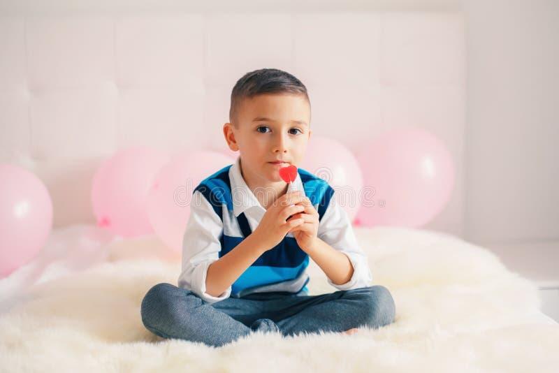 a criança adorável bonito do menino que come o coração deu forma ao pirulito que comemora Valentine Day foto de stock
