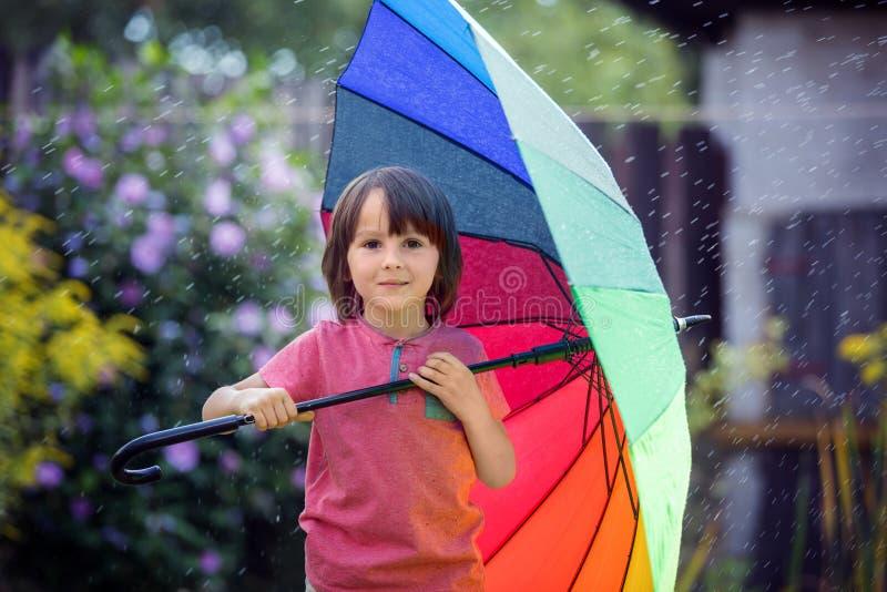 Criança adorável bonito, menino, jogando com o guarda-chuva colorido sob s fotos de stock