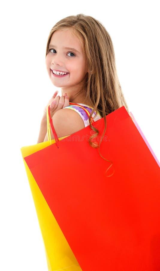 Criança adorável da menina que guarda sacos de papel coloridos de compra fotos de stock