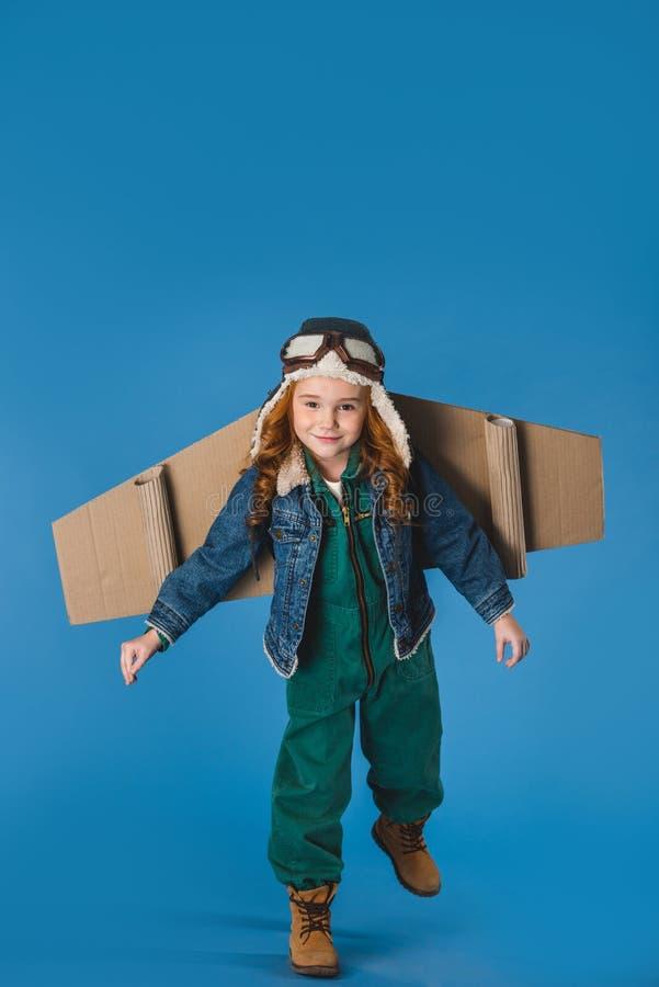 criança adorável do preteen no traje piloto com as asas planas de papel foto de stock