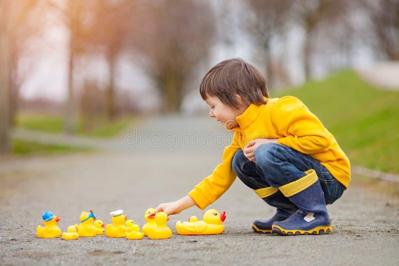 Criança adorável, menino, jogando no parque com patos de borracha, tendo f fotos de stock royalty free