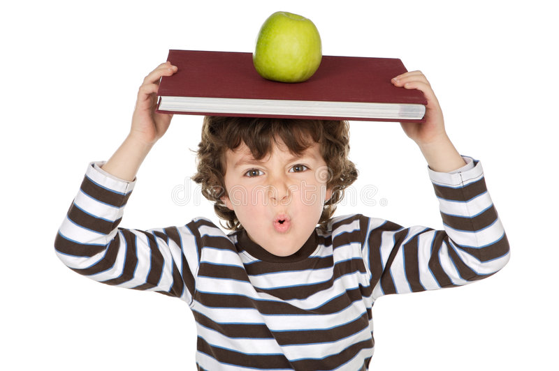Criança adorável que estuda com livros e maçã na cabeça imagens de stock royalty free