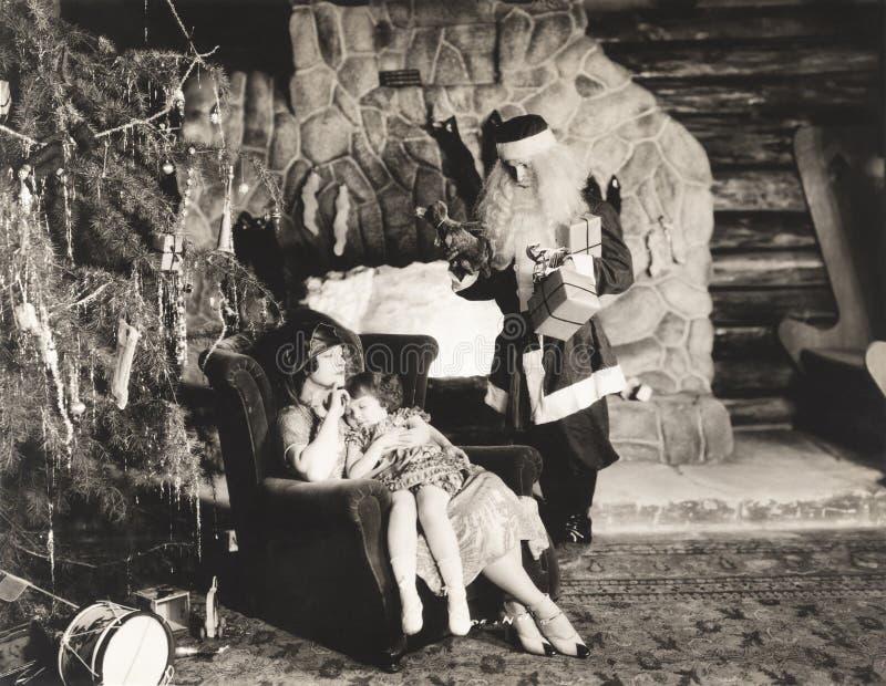 Criança adormecida no regaço da mãe como relógios de Santa Claus foto de stock