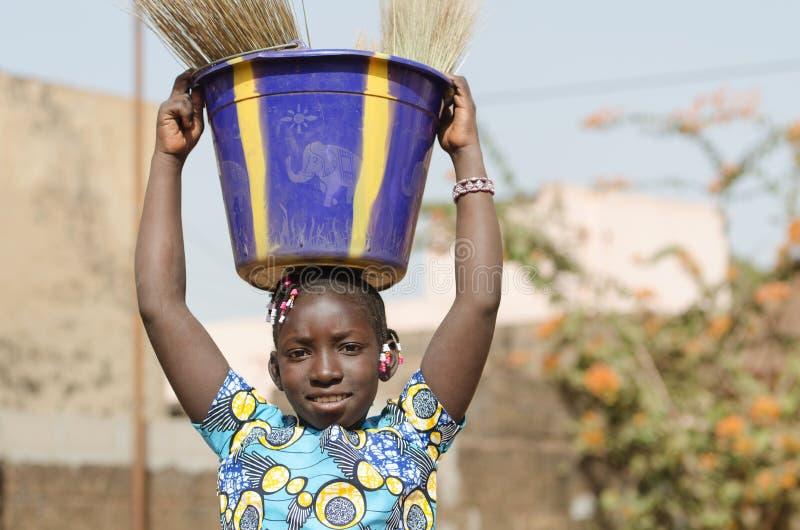 Criança africana bonita que ajuda sua família - símbolo dos trabalhos infanteis imagens de stock