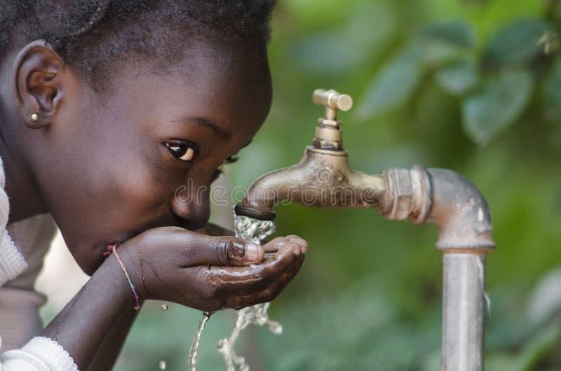 Criança africana bonita que bebe de um símbolo da escassez do água da torneira